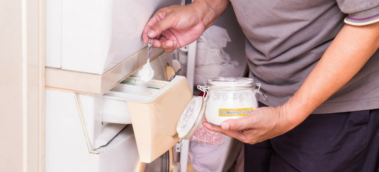 Man pouring baking soda in washing machine to get rid of the bad smell naturally.