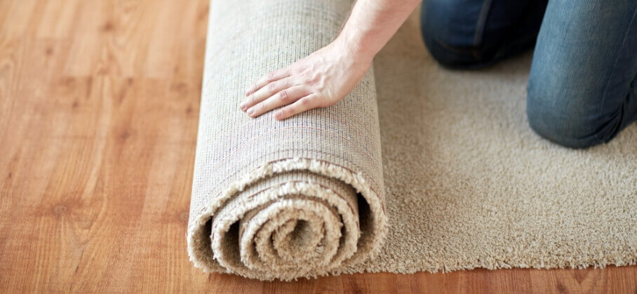 A woman fixing a carpet ripple.