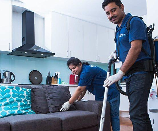 One off cleaning team in a flat, cleansing couch and carpet