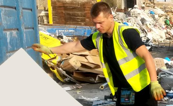 Technician collecting building waste for disposal.