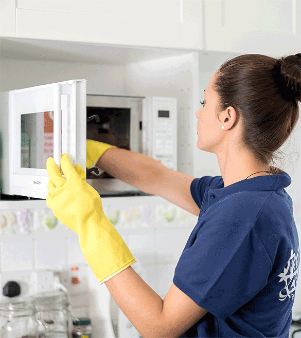 Maid cleaning a microwave