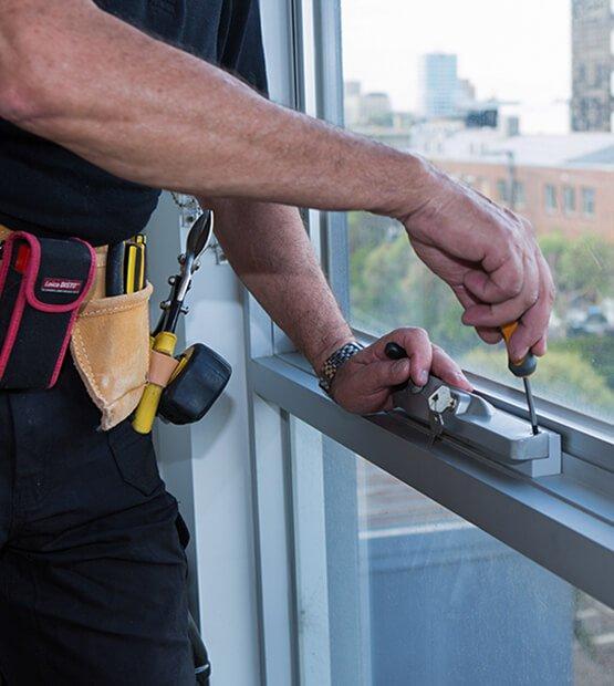 Fantastic Handyman fixing a window lock