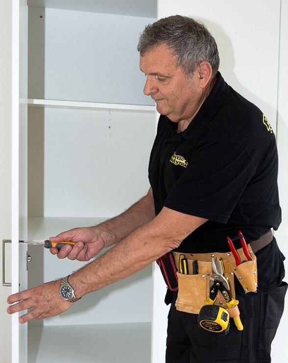 handyman fixing a wardrobe handle