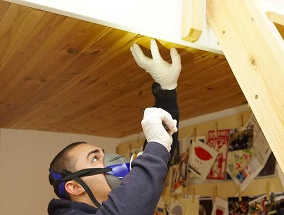 Termite Control: A pest controller inspecting a wooden ceiling for termites